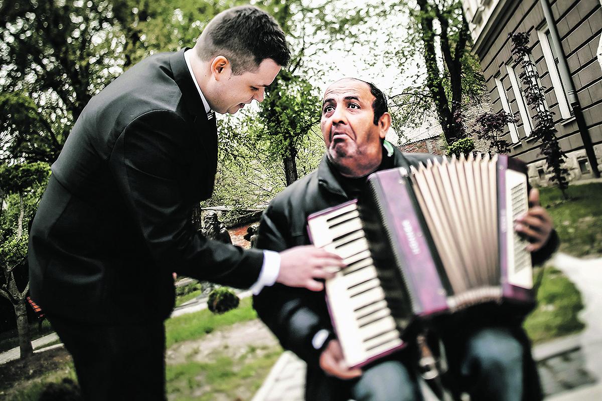 Slavonski Brod, 220417.  Ulicni svirac Stanoje Jovanovic rodjen je prije 52 godine u Slavonskom Brodu u kojem i danas zivi. Veliki je zaljubljenik u glazbu tako da svoju harmoniku svira iz ljubavi a ne zbog zarade. Osim sto svojom svirkom zabavlja prolaznike na ulici, svira i na zabavama i festama. Prije 14 godina se rastao, ima sina i kcer. Pati od depresije ali mu sviranje i gledanje prolaznika bas uvijek popravi raspolozenje. Ovim putem pozdravlja sve svoje Brodjane. Na fotografiji: ulicni svirac Stanoje Jovanovic ustupio je svoju harmoniku mladozenji Josipu Domoradu da odsvira par taktova svojoj buducoj zeni Danijeli Kuzmic. Foto: Danijel Soldo / CROPIX