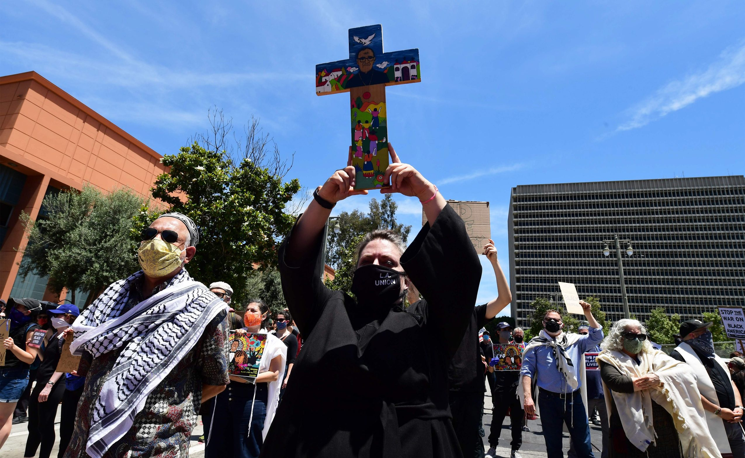 TOPSHOT - Pastor Bridie Roberts from the Hollywood United Methodist Church holds up a cross while joining Interfaith leaders and others during a memorial service honoring George Floyd and demanding justice for those killed at the hands of the police in downtown Los Angeles, California, on June 8, 2020. - Demonstrations continued across the nation as protesters began focusing their initial outrage over the death of the unarmed Floyd into demands for police reform and social justice. (Photo by Frederic J. BROWN / AFP)