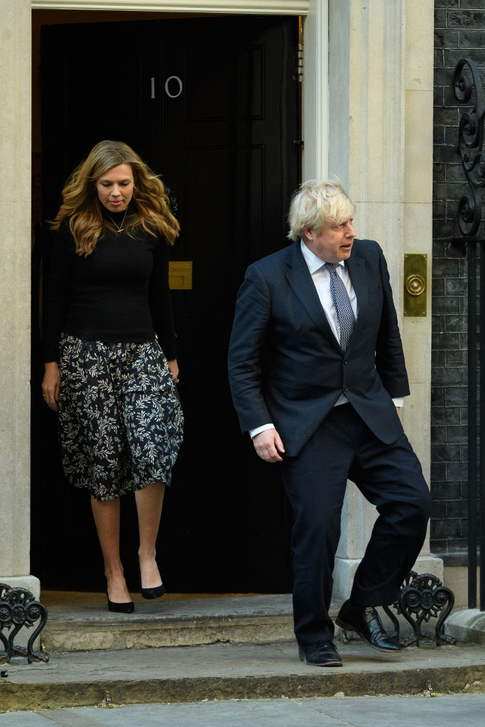 LONDON, UNITED KINGDOM - MAY 14: Britain's Prime Minister Boris Johnson and his partner Carrie Symonds stand outside the door of number 10 Downing Street as they thank the key workers who are working during the current lockdown on May 14, 2020 in London, United Kingdom. Following the success of  the
