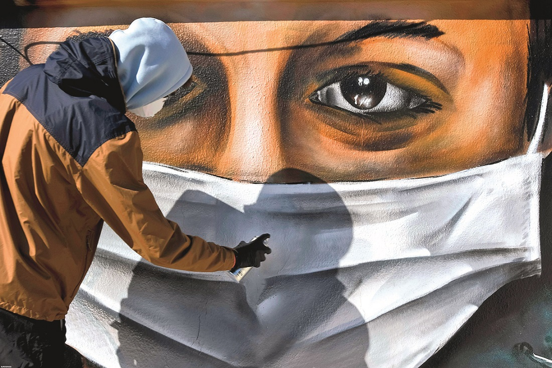 Athens, Greece - March 17, 2020: A young man is doing a graffiti inspired by the measures against coronavirus (COVID-19) at the terrace of a block of flats in Vouliagmeni street,Image: 508348008, License: Royalty-free, Restrictions: , Model Release: no, Credit line: VASILIS VERVERIDIS / Alamy / Alamy / Profimedia