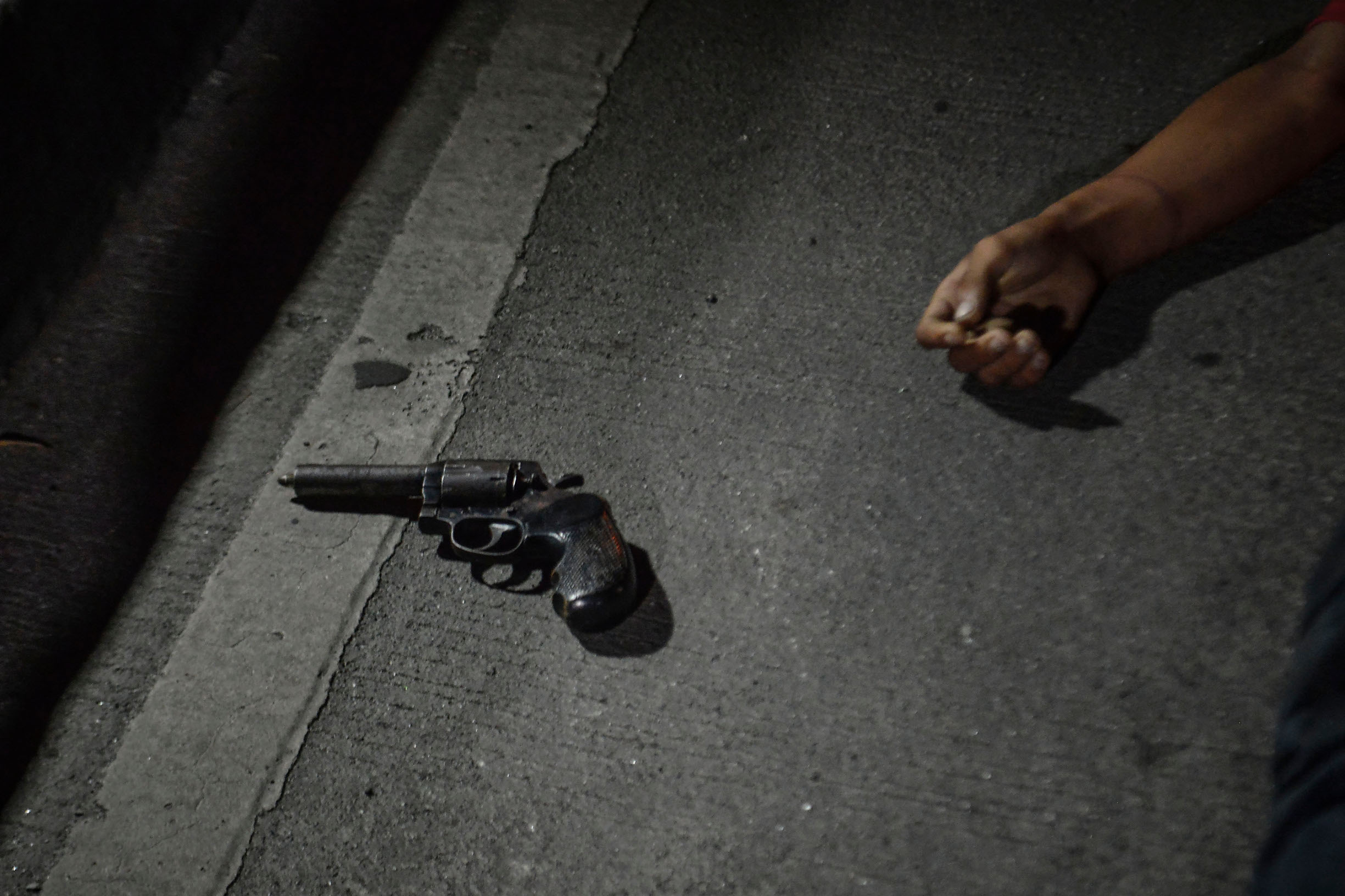 A revolver lies next to the body of a man who was killed by police during a police operation in Manila, Philippines, August 17, 2017. Amidst the drug crackdown's deadliest week yet, the shooting of a 17 year old schoolboy has sparked outrage over the drug war killings that has claimed more than 13,000 lives in one year. According to police, Kian Loyd Delos Santos fought back against police operatives during an anti-illegal drugs operation, but several witnesses and security footage saw Delos Santos being dragged away by plainclothes police to a dark lot where he was killed. Forensic evidence also suggests that Delos Santos did not fire a weapon. Thousands marched the streets during Delos Santos' funeral in what was the biggest demonstration yet condemning the thousands of cases of extrajudicial killings under President Rodrigo Duterte's war on drugs.  (Photo by Ezra Acayan/NurPhoto)