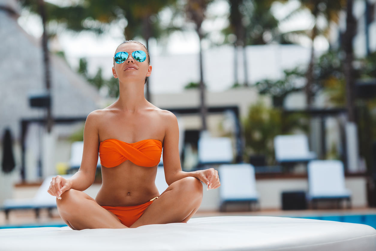 Elegant woman in bikini on sun-tanned slim and shapely body posing near swimming pool. Gorgeous young woman meditating in orange bikini sitting near the pool in the Lotus posture in the mirror-blue glasses