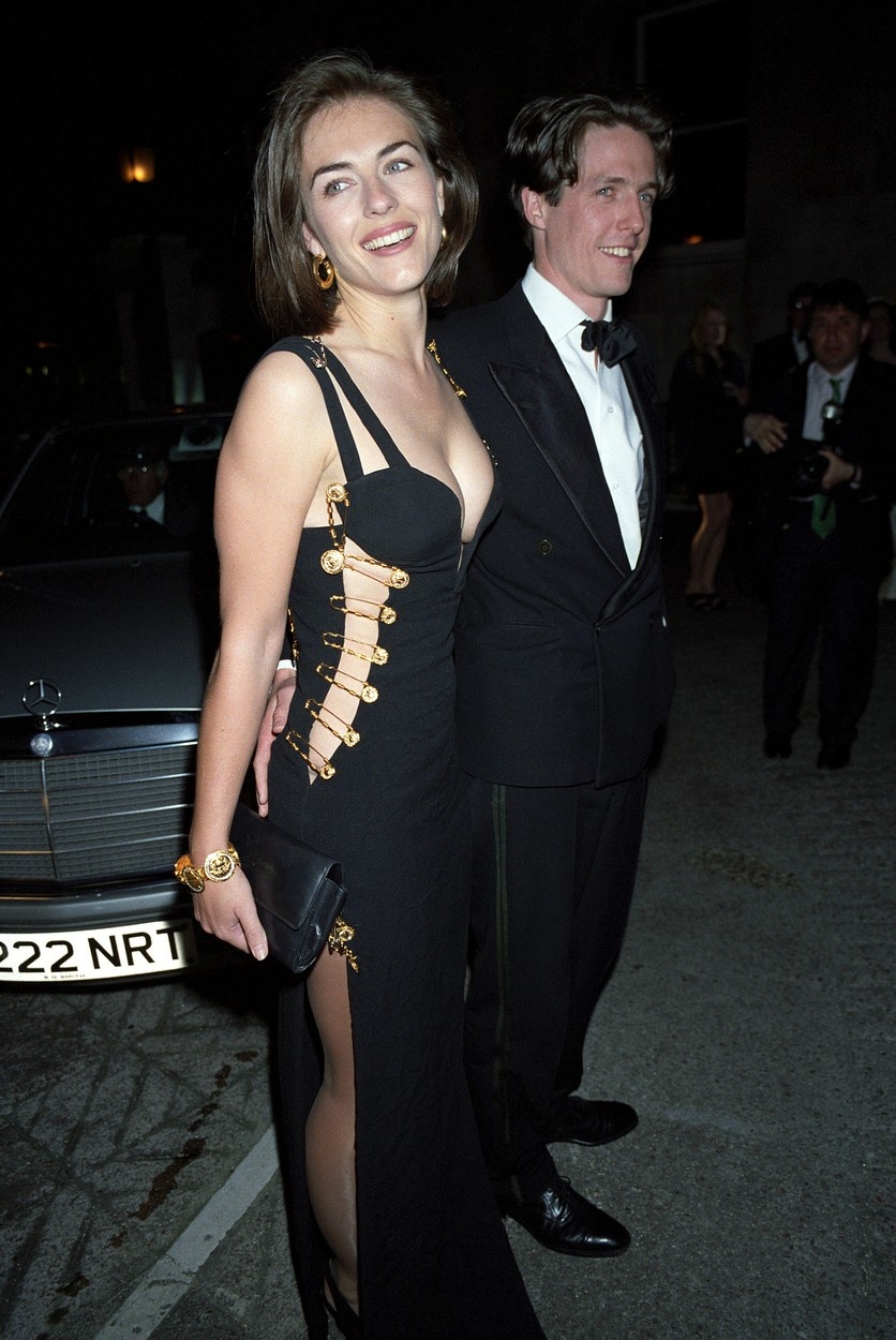 HUGH GRANT + LIZ HURLEY IN VERSACE PIN DRESS AT PARTY PREMIERE OF 'FOUR WEDDINGS AND A FUNERAL' 'FOUR WEDDING AND A FUNERAL' PREMIERE PARTY  BLACK VERSAGE DRESS WITH GOLD SAFTETY PINS / CLEAVAGE ELIZABETH,Image: 225089769, License: Rights-managed, Restrictions: , Model Release: no, Credit line: Richard Young Photographi / Shutterstock Editorial / Profimedia
