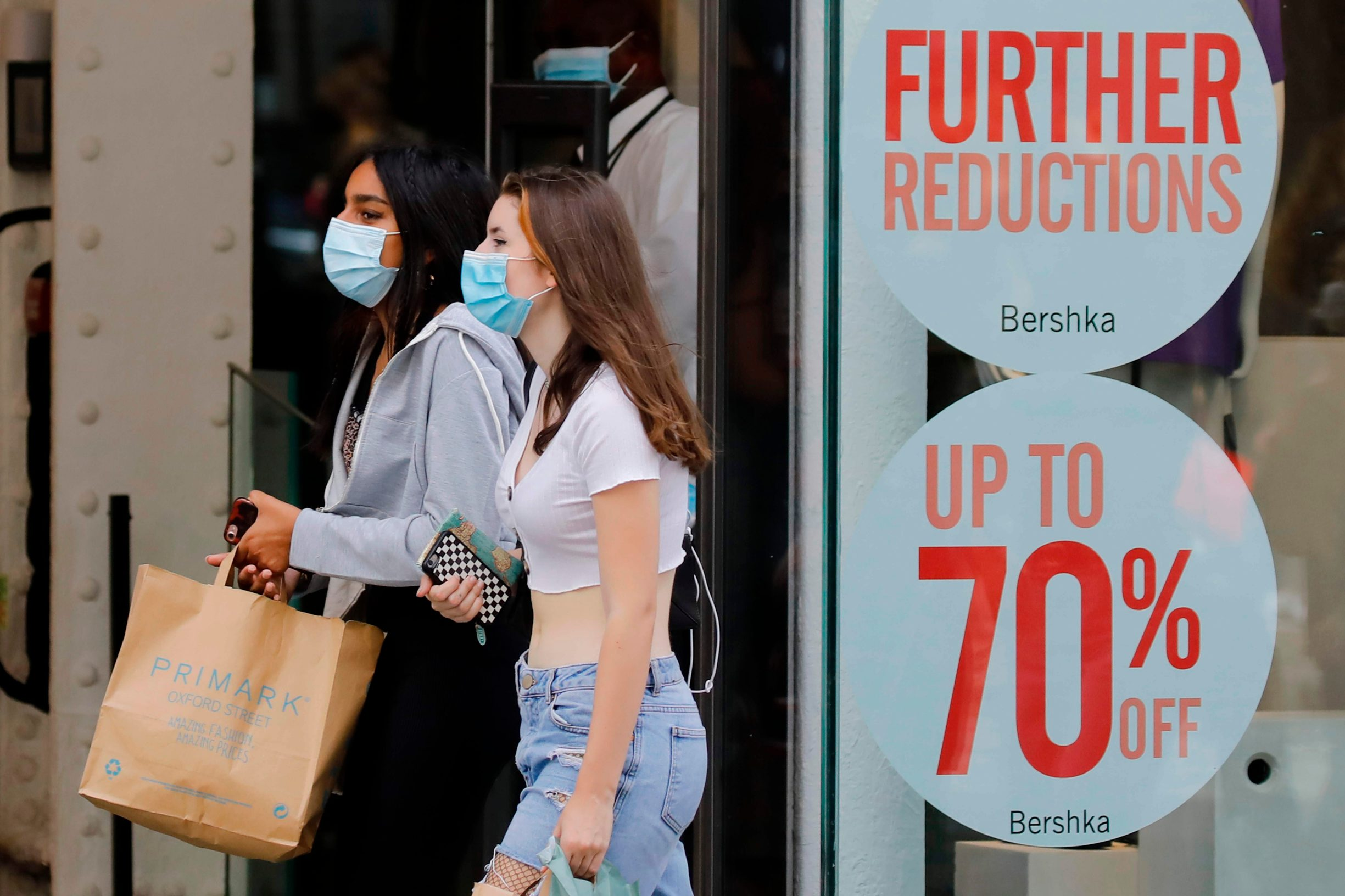 (FILES) In this file photo taken on July 24, 2020 Shoppers wear face masks on Oxford Street om London on July 24, 2020, after wearing facemasks in shops and supermarkets became compulsory in England as a measure to combat the spread of the novel coronavirus. - Britain's economy contracted by a record 20.4 percent in the second quarter with the country in lockdown over the coronavirus pandemic, official data showed on August 12, 2020. (Photo by Tolga AKMEN / AFP)