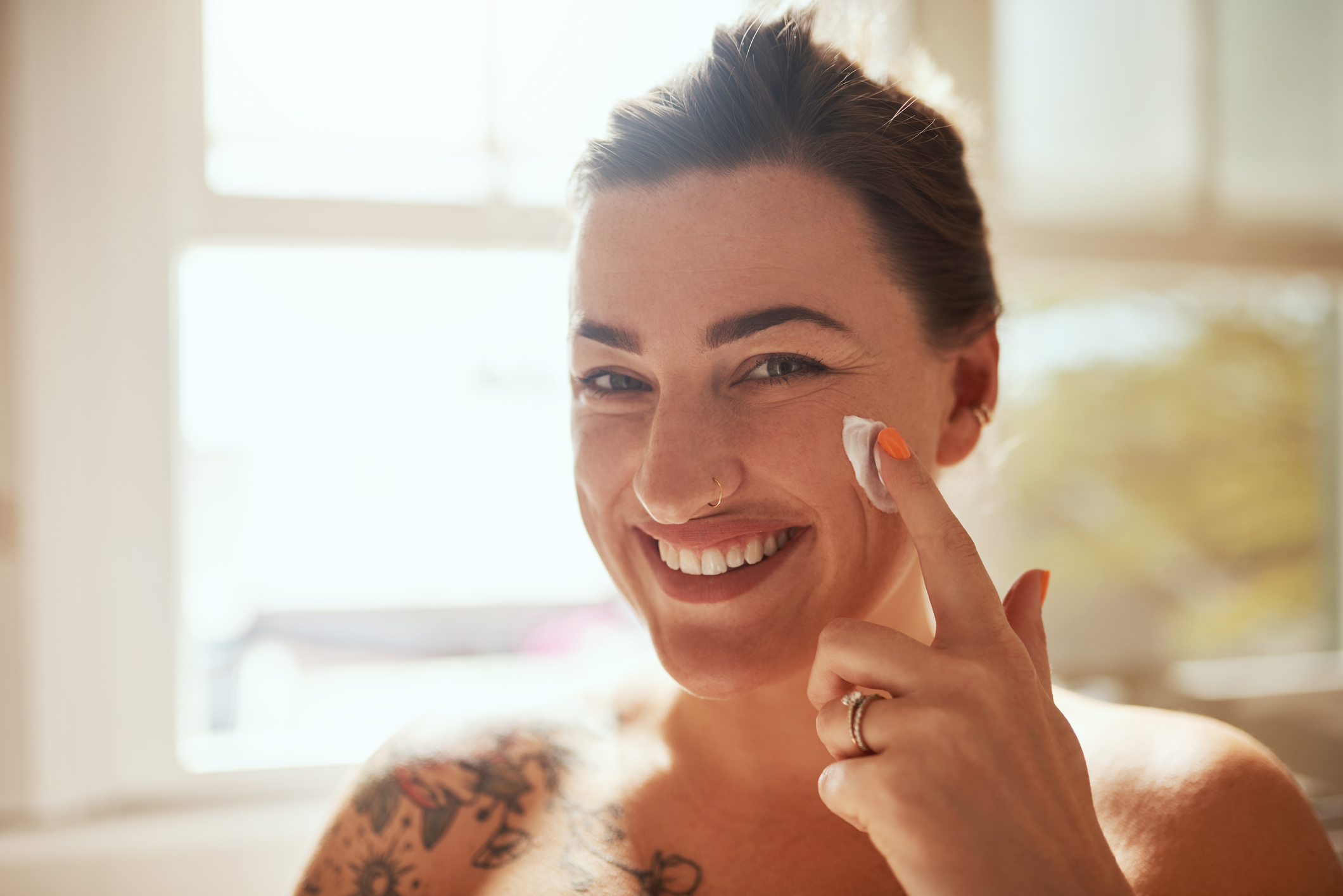 Shot of an attractive young woman applying moisturiser during her morning beauty routine
