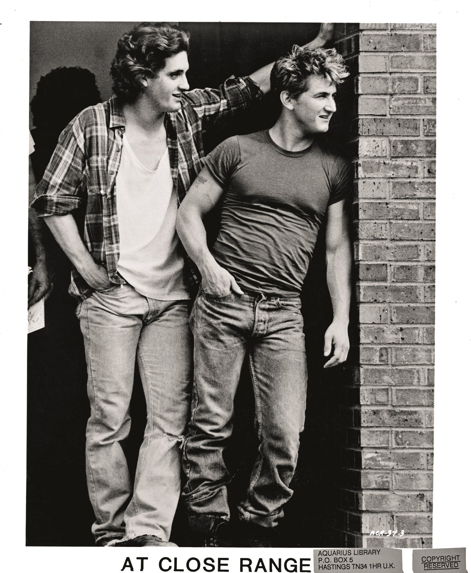 Chris Penn and Sean Penn looking around brick wall in a scene from the film 'At Close Range', 1986. (Photo by Orion/Getty Images)