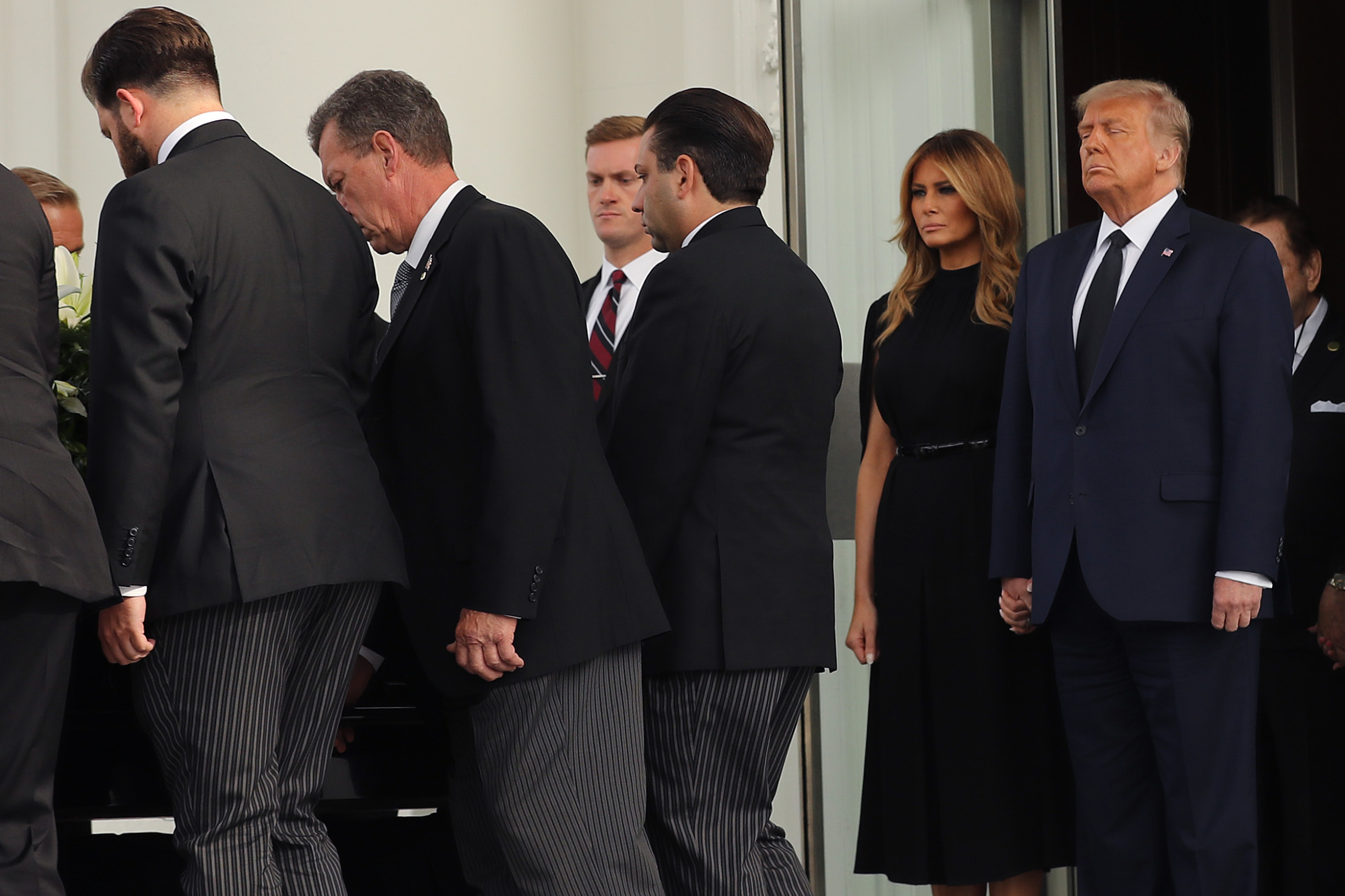 """WASHINGTON, DC - AUGUST 21: U.S. President Donald Trump (R) and First Lady Melania Trump follow his brother Robert Trump's casket out of the White House following his funeral service on August 21, 2020 in Washington, DC. Robert Trump passed away on August 15 at the age of 71. In a statement, President Trump wrote, """"He was not just my brother, he was my best friend."""