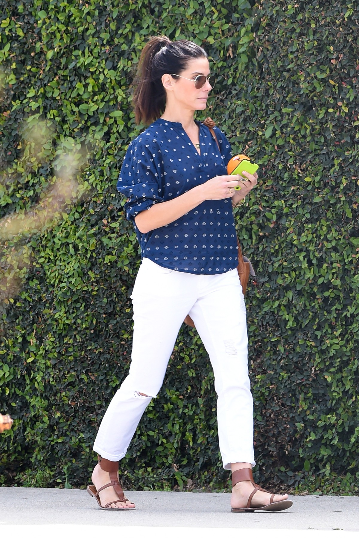 *EXCLUSIVE* Los Angeles, CA - Actress and busy mother Sandra Bullock spent the day at a Sound Studio where she kept herself busy doing voice-over work for her character Scarlett Overkill for the upcoming animation film 'The Minions', she kept her look simple with a navy blue and white polka dot blouse, white trousers and strappy sandals matching her brown leather tote bag.           April 10, 2014,Image: 190114958, License: Rights-managed, Restrictions: NO Brazil,NO Brazil, Model Release: no, Credit line: AKM Images / Backgrid USA / Profimedia
