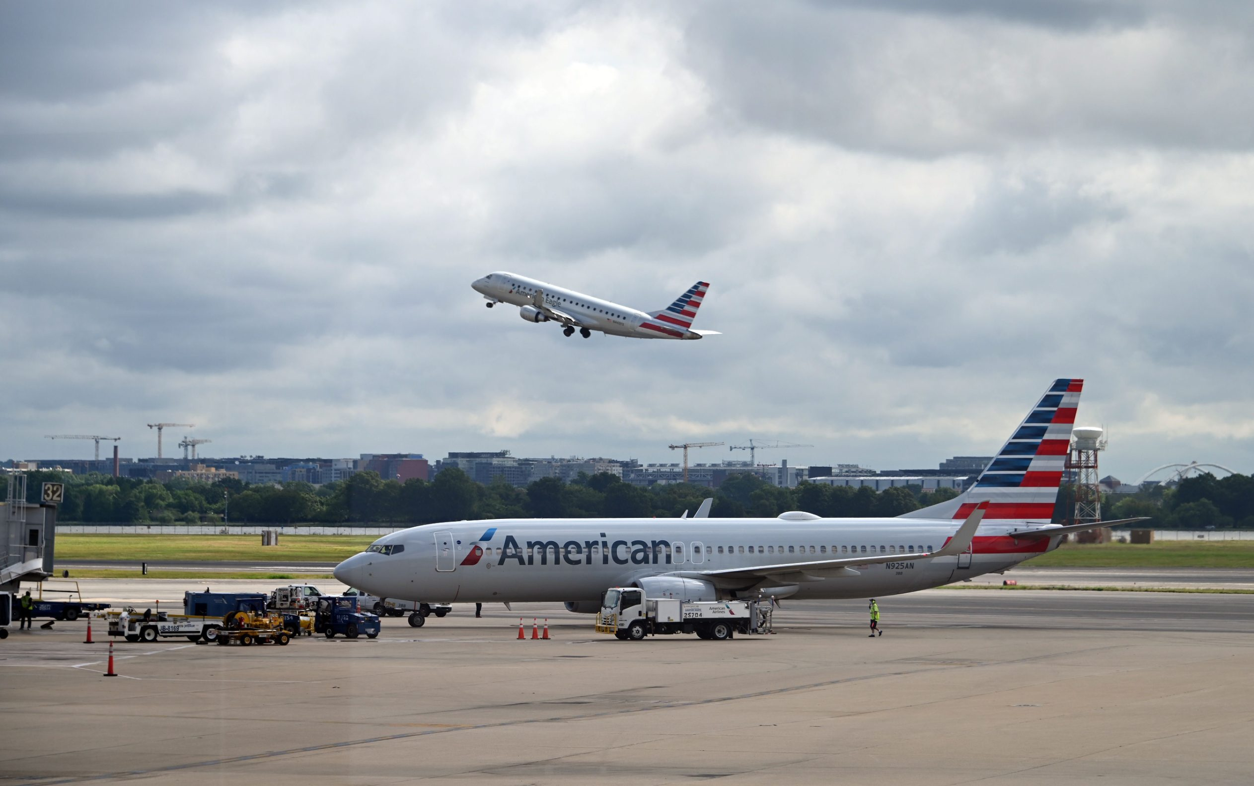 (FILES) In this file photo an American Eagle plane takes off while an American Airlines plane approaches a gate at Ronald Reagan Washington National Airport on July 10, 2020, in Arlington, Virginia, during the coronavirus pandemic. - American Airlines said on August 25, 2020 it will lay off 19,000 workers on October 1, in addition to thousands more who left the company or agreed to voluntary furloughs, unless Congress offers more aid.