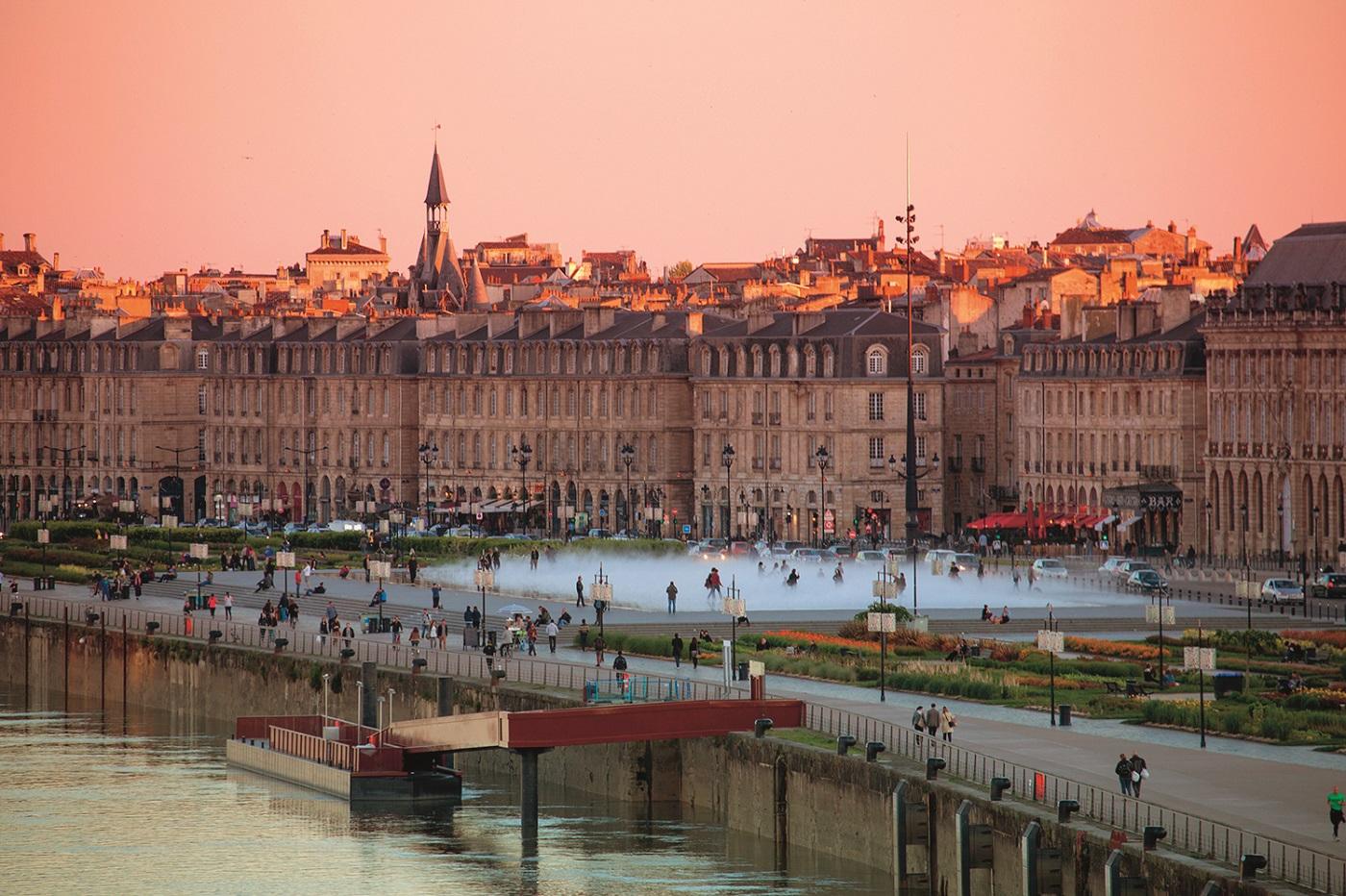 Miroir d'Eau water mirror fountain at Place de la Bourse and city buildings at sunset, Bordeaux, Gironde, Aquitane, France.