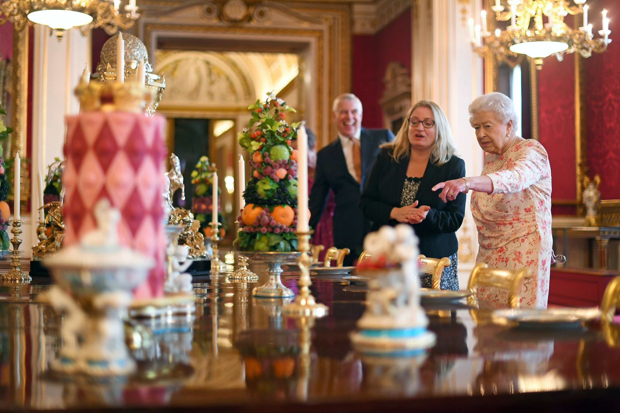 LONDON, ENGLAND - JULY 17: Queen Elizabeth II looks at a recreation of the 'Victoria' pattern dessert service in the State Dining Room, as part of the exhibition to mark the 200th anniversary of the birth of Queen Victoria for the Summer Opening of Buckingham Palace on July 17, 2019 in London, England. (Photo by Victoria Jones - WPA Pool/Getty Images)