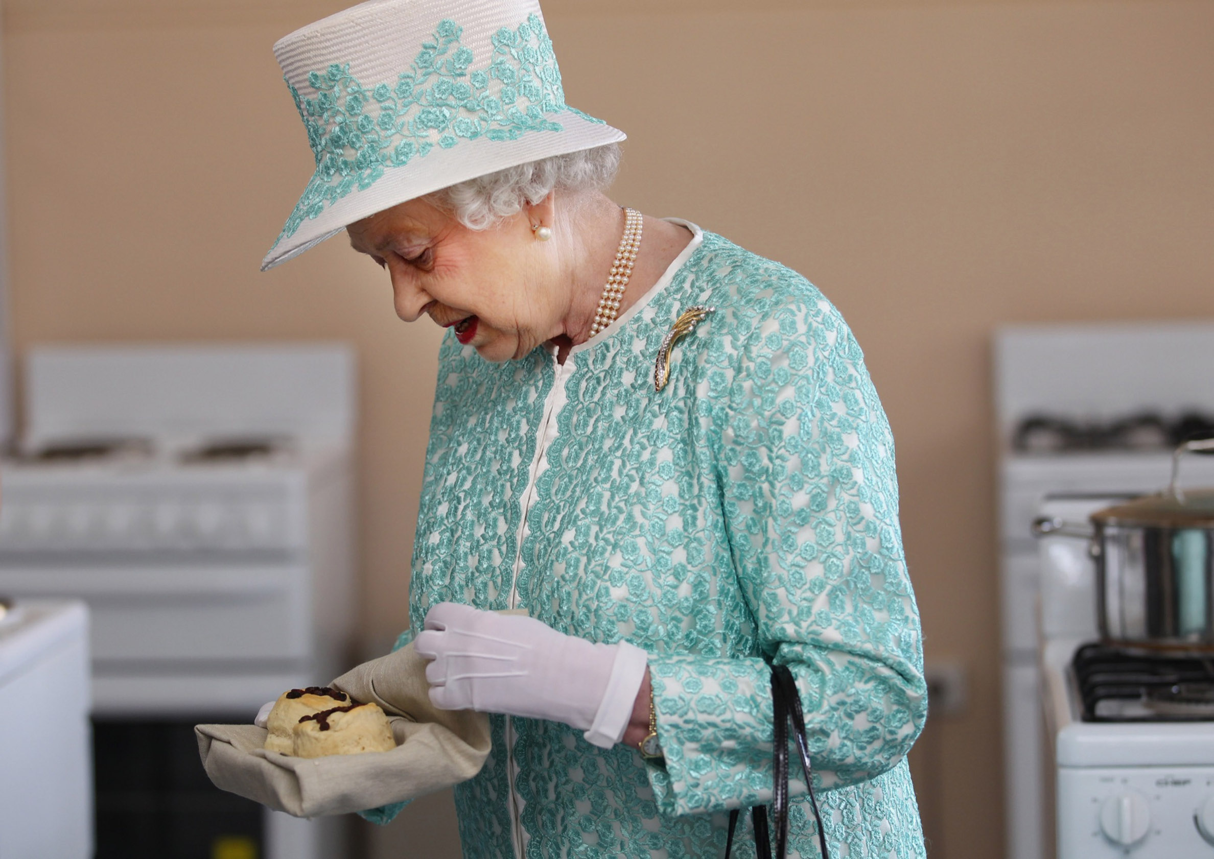PERTH, AUSTRALIA - OCTOBER 27:  Queen Elizabeth II receives scones from the Clontarf kitchen during her visit to Clontarf Aboriginal college on October 27, 2011 in Perth, Australia. The Queen and Duke of Edinburgh are on a 10-day visit to Australia and will travel to Canberra, Brisbane, and Melbourne before heading to Perth for the Commonwealth Heads of Government meeting. This is the Queen's 16th official visit to Australia. (Photo by Sharon Smith-Pool/Getty Images)