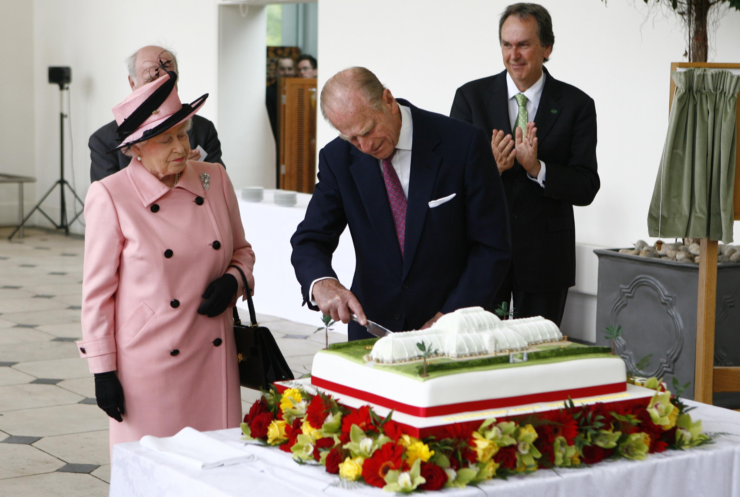 LONDON - MAY 5: Prince Philip, Duke of Edinburgh cuts a cake as Queen Elizabeth II looks on during a visit to The Royal Botanic Gardens in Kew on May 5, 2009 in London, England.  The Royal Botanic Gardens at Kew was celebrating it's 250th Anniversary.  (Photo by Johnny Green - WPA Pool/Getty Images)