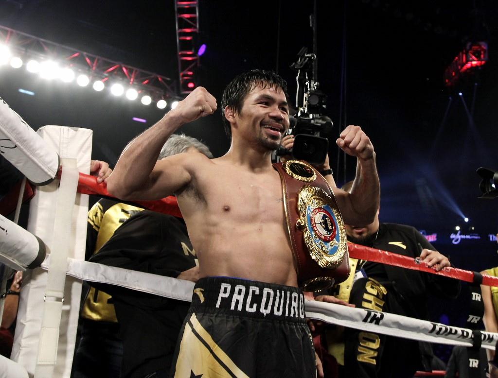 Boxer Manny Pacquiao of the Philippines celebrates after beating Jessie Vargas with a unanimous decision to win the WBO welterweight championship at the Thomas & Mack Center in Las Vegas, Nevada on November 5, 2016. (Photo by John GURZINSKI / AFP)