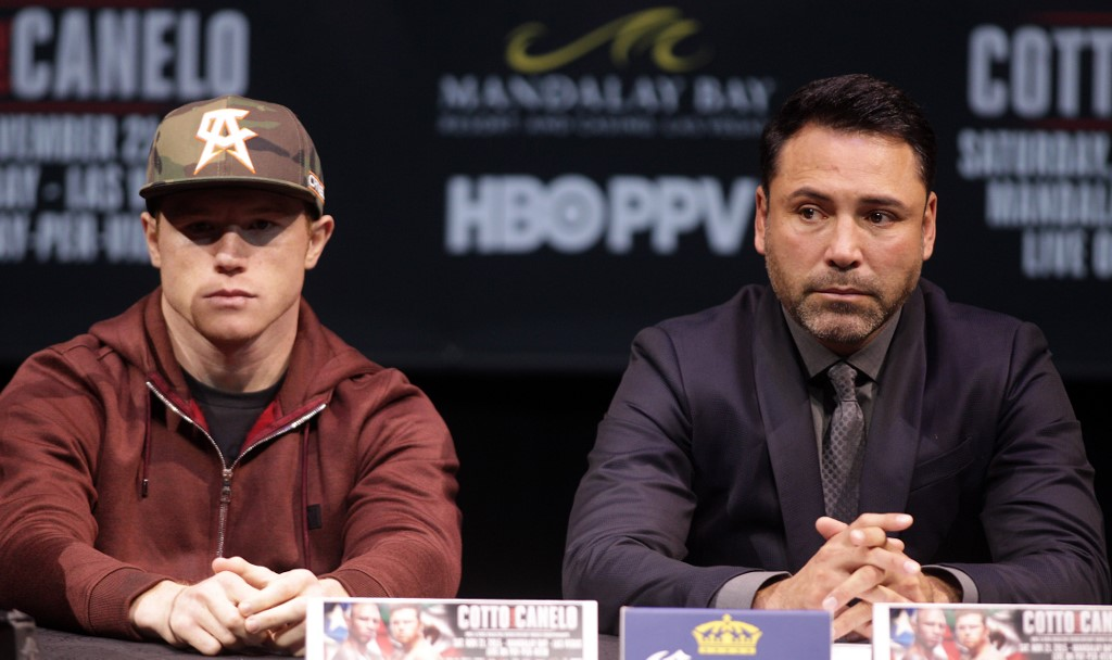 Two time world champion, Saul 'Canelo' Alvarez, Guadalajara, Mexico and promoter Oscar De La Hoya listen to former WBC Middleweight World Champion Miguel Cotto, Puerto Rico during their press conference in Las Vegas, Nevada on November 18, 2015.  Cotto was stripped of his World Boxing Council middleweight world title on Tuesday, days before his anticipated bout against Mexican Saul Alvarez in Las Vegas on Saturday. Amid reports that Cotto declined to pay the USD 300,000 sanctioning fee for a title fight, the WBC said in a statement only that the Puerto Rican and his camp failed to comply with WBC regulations. AFP PHOTO/ John Gurzinski (Photo by JOHN GURZINSKI / AFP)