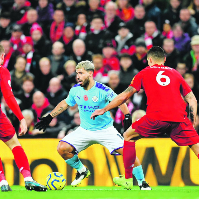 Manchester City's Argentinian striker Sergio Aguero (C) vies with Liverpool's English midfielder Jordan Henderson (L) and Liverpool's Croatian defender Dejan Lovren (R) during the English Premier League football match between Liverpool and Manchester City at Anfield in Liverpool, north west England on November 10, 2019. (Photo by Paul ELLIS/AFP)/RESTRICTED TO EDITORIAL USE. No use with unauthorized audio, video, data, fixture lists, club/league logos or 'live' services. Online in-match use limited to 120 images. An additional 40 images may be used in extra time. No video emulation. Social media in-match use limited to 120 images. An additional 40 images may be used in extra time. No use in betting publications, games or single club/league/player publications. /