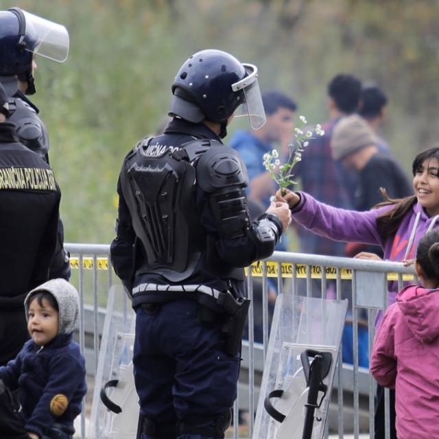 An Iranian migrant child Asal is seen across the iron barricade giving a flower to a Bosnian border police officer, on October 26, 2018 near Velika Kladusa town in Bosnia and Herzegovina. Hundreds of migrants including women and children continue their waiting around the border crossing between Bosnia and Croatia, to cross into neighboring Croatia, a member of the European Union.