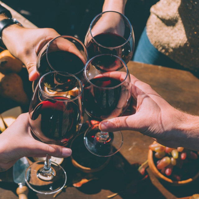 cropped shot of group of people clinking glasses of delicious red wine