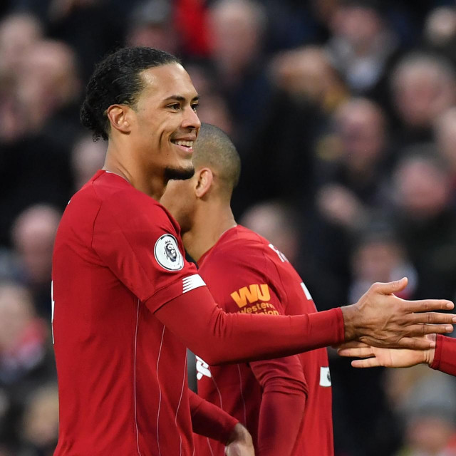 Liverpool's English midfielder Jordan Henderson (R) celebrates with Liverpool's Dutch defender Virgil van Dijk after scoring his team's second goal during the English Premier League football match between Liverpool and Southampton at Anfield in Liverpool, north west England on February 1, 2020. (Photo by Paul ELLIS/AFP)/RESTRICTED TO EDITORIAL USE. No use with unauthorized audio, video, data, fixture lists, club/league logos or 'live' services. Online in-match use limited to 120 images. An additional 40 images may be used in extra time. No video emulation. Social media in-match use limited to 120 images. An additional 40 images may be used in extra time. No use in betting publications, games or single club/league/player publications./