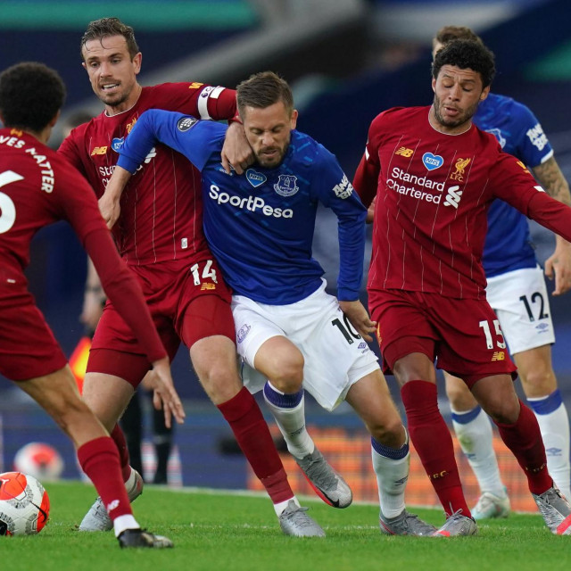 TOPSHOT - Everton's Icelandic midfielder Gylfi Sigurdsson (C) vies for the ball against Liverpool's English midfielder Alex Oxlade-Chamberlain (R) and Liverpool's English midfielder Jordan Henderson (2nd L) during the English Premier League football match between Everton and Liverpool at Goodison Park in Liverpool, north west England on June 21, 2020. (Photo by Jon Super/POOL/AFP)/RESTRICTED TO EDITORIAL USE. No use with unauthorized audio, video, data, fixture lists, club/league logos or 'live' services. Online in-match use limited to 120 images. An additional 40 images may be used in extra time. No video emulation. Social media in-match use limited to 120 images. An additional 40 images may be used in extra time. No use in betting publications, games or single club/league/player publications./