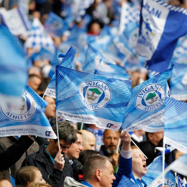 (FILES) In this file photo taken on May 11, 2013 Wigan Athletic fans wave flags before the start of the English FA Cup final football match between Manchester City and Wigan Athletic at Wembley Stadium in London. - Championship side Wigan will be handed a 12-point deduction after entering administration as the impact of the coronavirus pandemic starts to bite in English football. (Photo by IAN KINGTON/AFP)