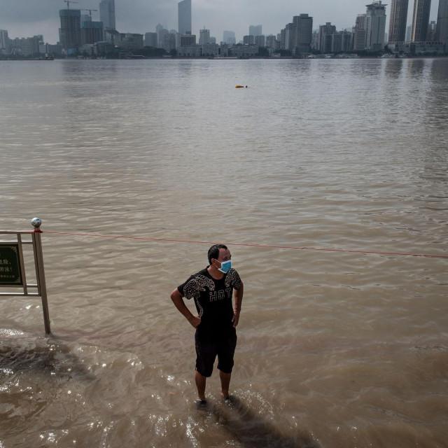 Muškarac na poplavljenim ulicama pored rijeke Yangtze