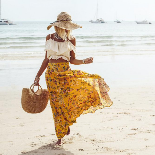 Girl wearing floral maxi skirt walking barefoot on the sea shore, Thailand, Phuket. Bohemian clothing style.