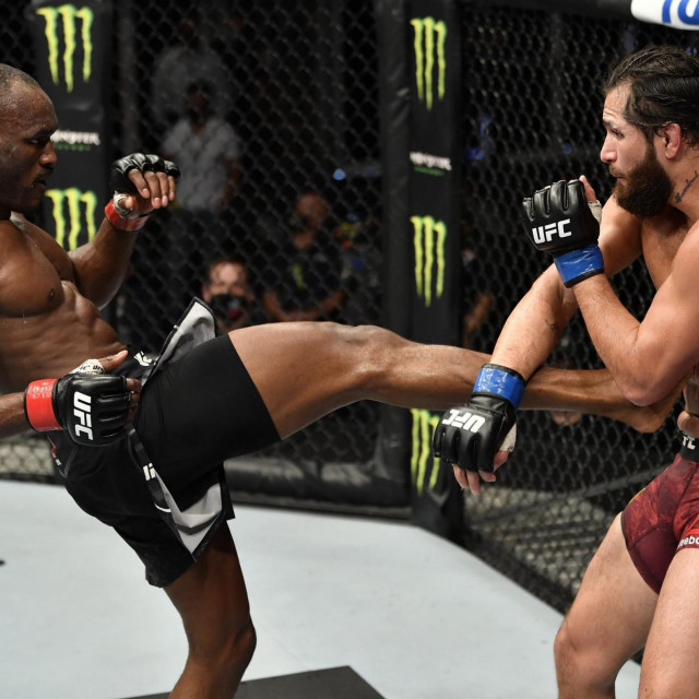 """A handout image released by the Ultimate Fighting Championship (UFC) on July 12, 2020, shows Nigeria's Kamaru Usman (L) kicking US' Jorge Masvidal in their welterweight championship fight during the UFC 251 event at UFC Fight Island in Abu Dhabi's Yas Island. (Photo by Jeff BOTTARI/ZUFFA LLC/AFP)/=== RESTRICTED TO EDITORIAL USE - MANDATORY CREDIT """"AFP PHOTO/HO/ZUFFA LLC"""" - NO MARKETING NO ADVERTISING CAMPAIGNS - DISTRIBUTED AS A SERVICE TO CLIENTS ==="""