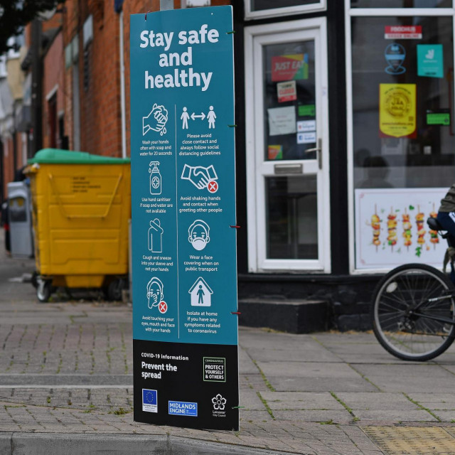 "A youth cycles past a sign telling local residents to ""Social Distance"" and advising on how to help ""Prevent the Spread"" of coronavirus, in the North Evington district of Leicester, central England, on June 29, 2020. - The central English city of Leicester could be the country's first to face a local lockdown due to a rise in coronavirus cases, the UK's Home Secretary Priti Patel said on June 28. The Midlands city recorded 658 new cases in the two weeks up to June 16, many linked to fresh outbreaks at food production plants. (Photo by Ben STANSALL/AFP)"