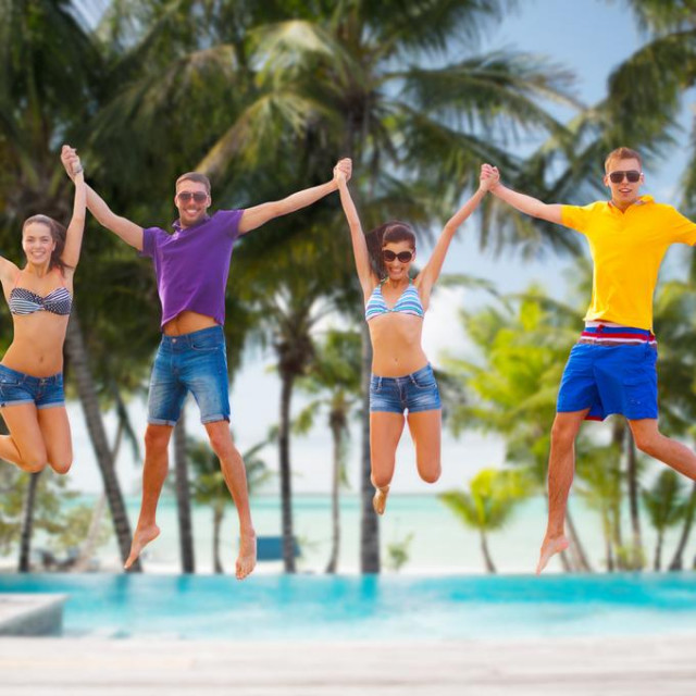 Young and happy people jumping into the pool