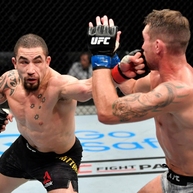 "In this handout image released by the Ultimate Fighting Championship (UFC), Robert Whittaker of New Zealand punches Darren Till of England in their middlewweight championship fight during the UFC 251 event at UFC Fight Island in Abu Dhabi's Yas Island on July 26, 2020. (Photo by Jeff Bottari/Zuffa LLC/AFP)/XGTY/=== RESTRICTED TO EDITORIAL USE - MANDATORY CREDIT ""AFP PHOTO/HO/ZUFFA LLC"" - NO MARKETING NO ADVERTISING CAMPAIGNS - DISTRIBUTED AS A SERVICE TO CLIENTS ==="