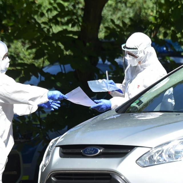 Zdravstveni radnici testiraju ljude iz automobila u Mammingu u južnoj Njemačkoj nakon izbijanja virusa na obližnjoj farmi 27.srpnja 2020.<br />