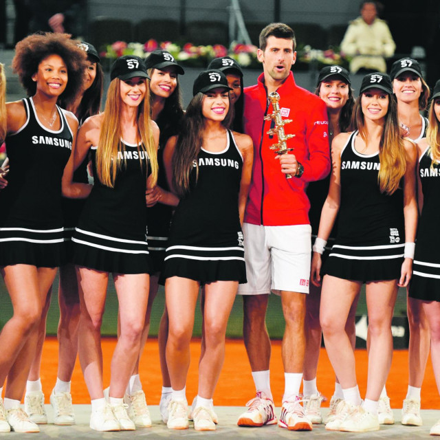 Serbia's Novak Djokovic poses with ball girls after beating Britain's Andy Murray during the Madrid Open men's tennis final at the Caja Magica (Magic Box) sports complex in Madrid on May 8, 2016. (Photo by GERARD JULIEN/AFP)