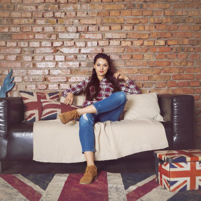Pretty hipster girl sitting on couch at home in the living room
