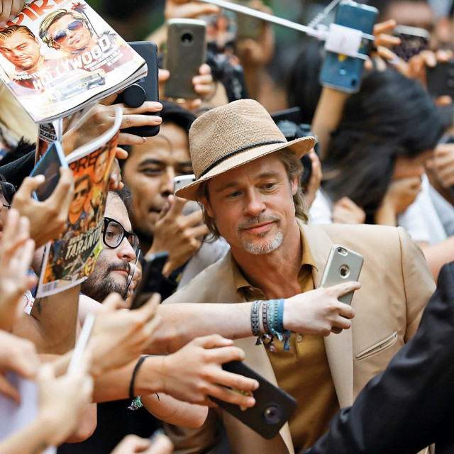 "MEXICO CITY, MEXICO - AUGUST 12: Brad Pitt signs autographs and takes selfies with fans during the ""Once Upon A Time In Hollywood"" Mexico City premiere red carpet at Toreo Parque Central on August 12, 2019 in Mexico City, Mexico. (Photo by Victor Chavez/Getty Images)"