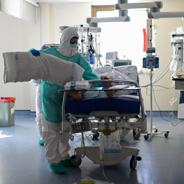 A healthcare worker in protective suit attends a COVID-19 patient at the Intensive Care Unit (ICU) of the Ramon y Cajal Hospital in Madrid on October 15, 2020. (Photo by OSCAR DEL POZO/AFP)