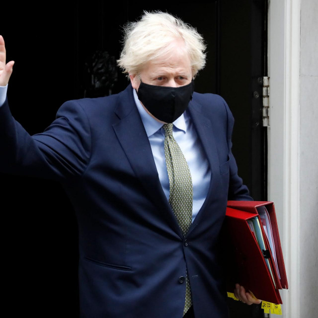 Britain's Prime Minister Boris Johnson wearing a face mask or covering due to the COVID-19 pandemic, waves as he leaves number 10 Downing Street in central London on October 14, 2020, to take part in the Prime Minister Question (PMQs) session in the House of Commons. (Photo by Tolga AKMEN/AFP)