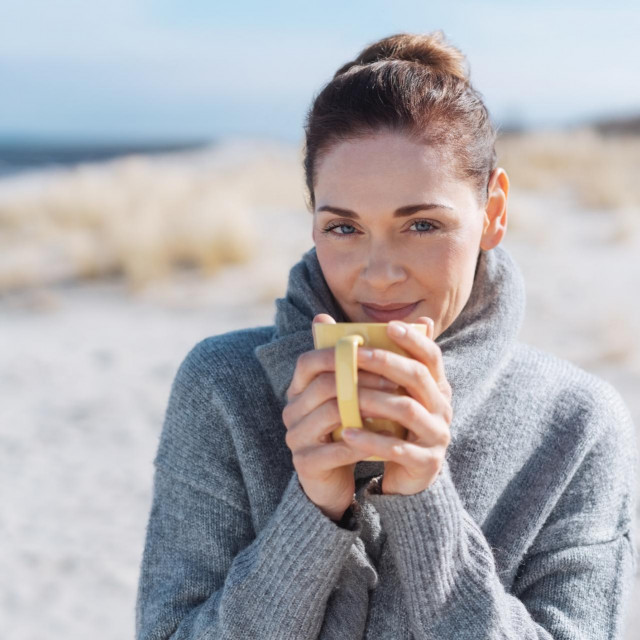 Smiling woman relaxing with coffee at the seaside standing on a sandy beach in a warm winter scarf smiling at the camera