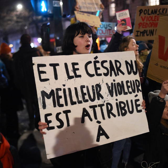 """A feminist activists holds a sign reading """"And the Cesar award for best rapist goes to..."""" during a demonstration outside the Salle Pleyel in Paris as guests arrive for the 45th edition of the Cesar Film Awards ceremony on February 28, 2020. - The academy organising France's Cesar awards is going through a crisis after the entire board resigned amid calls for reform and a row over the long-running Roman Polanski scandal. The Cesar Academy has been under fire since the end of January after Roman Polanski's film """"An Officer and a Spy"""" (J'accuse) topped the list of nominations for this year's Cesar awards, due to be handed out on February 28. Polanski told AFP on February 27, 2020, he would not attend the ceremony French Oscars because he fears a """"public lynching"""" by feminist activists. (Photo by Lucas BARIOULET/AFP)"""