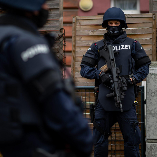 Policemen stand in front of a residential building in Linz, Austria, where a man was detained on November 3, 2020 in connection with the Vienna shooting one day before. - The only known gunman in the Vienna attack which left four people dead was a convicted supporter of the Islamic State group and had dual Macedonian-Austrian nationality, Austria's interior minister said. Police said it was not clear whether there were one or more attackers in the shooting rampage from November 2, 2020. Officers have carried out raids at 15 addresses and made at least one arrest in connection with the killings. (Photo by WERNER KERSCHBAUMMAYR/APA/AFP)/Austria OUT