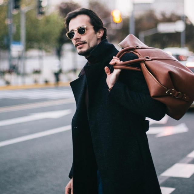 Handsome modern man on a lovely day out in the city. He is holding a bag.