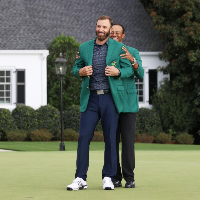 AUGUSTA, GEORGIA - NOVEMBER 15: Dustin Johnson of the United States is awarded the Green Jacket by Masters champion Tiger Woods of the United States during the Green Jacket Ceremony after winning the Masters at Augusta National Golf Club on November 15, 2020 in Augusta, Georgia. Rob Carr/Getty Images/AFP<br /> == FOR NEWSPAPERS, INTERNET, TELCOS & TELEVISION USE ONLY ==