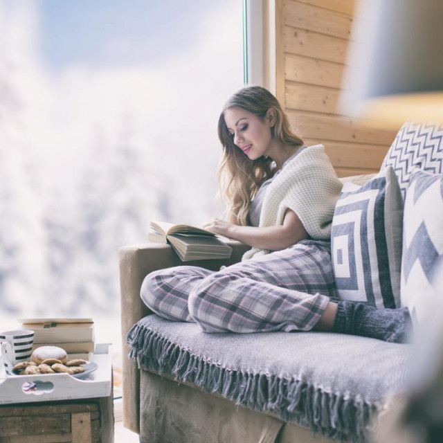 Young beautiful blonde woman with cup of coffee sitting home in living room by the window reading book. Winter snow landscape view. Christmas concept