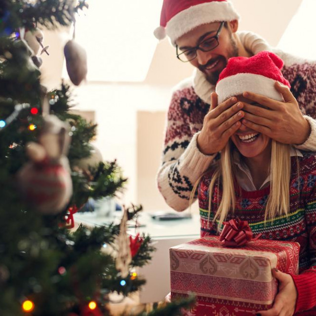 Cropped shot of a man surprising his girlfriend with a Christmas gift.<br /> <br /> B