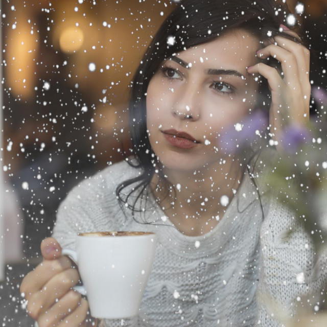 Beautiful Young Woman drinking coffee and watching snow through the window