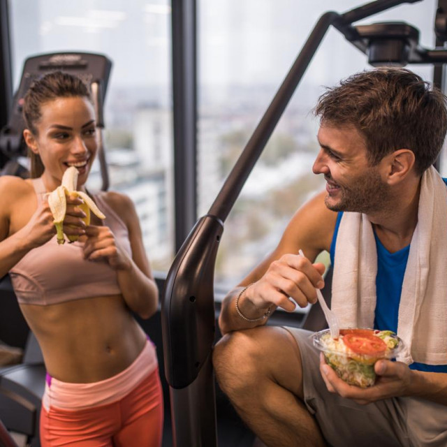 Happy athletes communicating while eating healthy food on a break in a health club. Focus is on man.