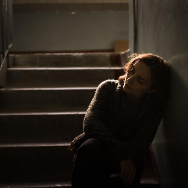 woman in a dark sweater at the steps, concept of loneliness and depression, selective focus, dark style, abstraction
