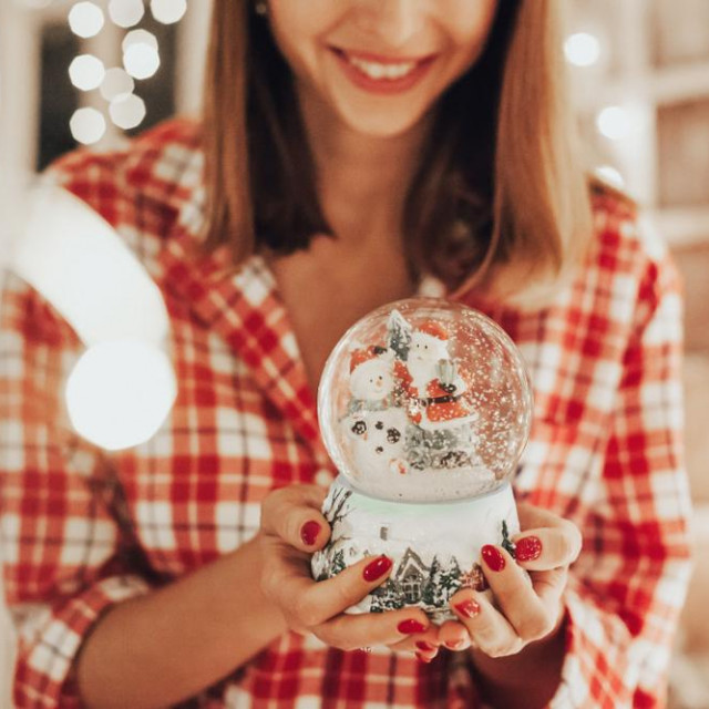 woman holding a snow globe