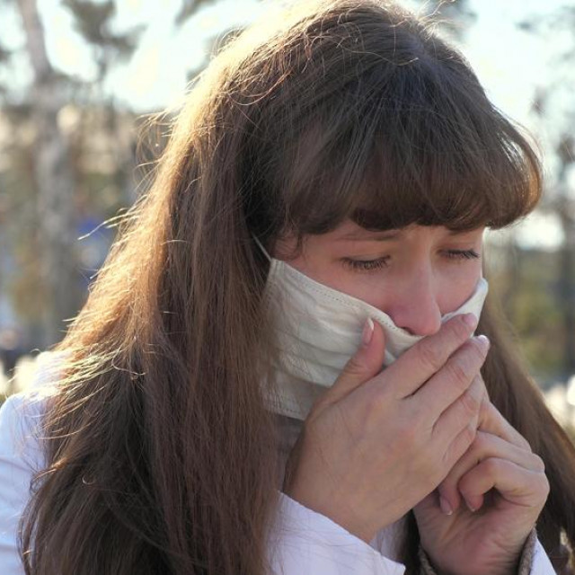 Young sick woman in medical protective mask coughs on street. girl is infected coughing. Carrier, Covid-19, coronavirus, symptom. Pandemic Coronavirus. a person with the flu. close-up
