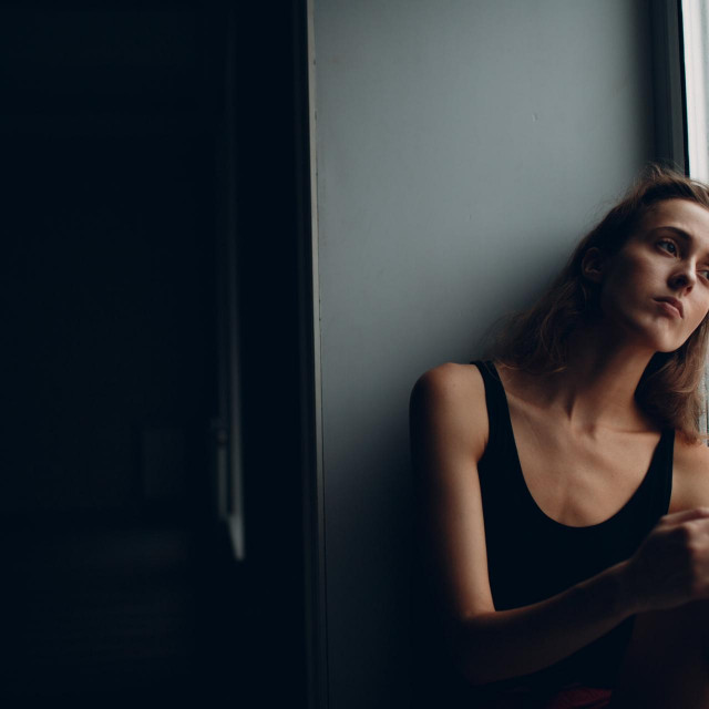 Portrait of young beautiful woman near misted window